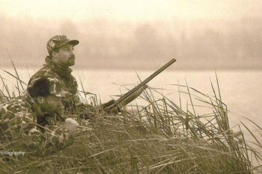 Picture of waterfowl hunters preparing as goose sets wings