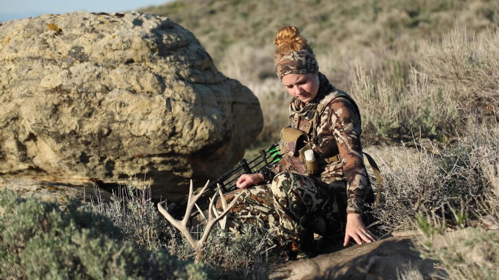 Jessi Johnson, a new hunter, somberly looks at a deer she just shot