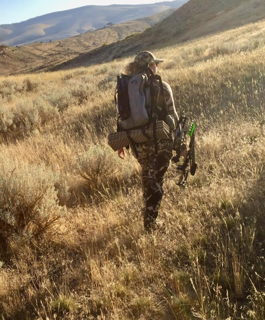 Photo of Jessi Johnson, a new hunter, walking through field with hunting pack and bow.